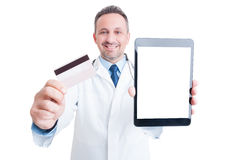 Confident medic showing credit card and blank screen tablet Royalty Free Stock Image