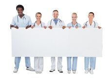 Confident medical team holding blank billboard Stock Images