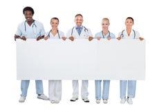 Confident medical team holding blank billboard. Full length portrait of confident medical team holding blank billboard over white background stock images
