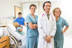 Confident Medical Team With Newborn Baby And Royalty Free Stock Image