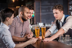 Confident men drinking beer in the bar. Men shout and rejoice in Stock Photos