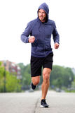 Confident middle age athlete running in street stock photo