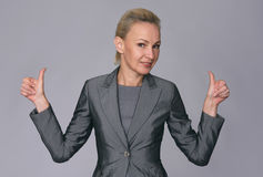 Confident middle aged businesswoman. Giving the thumbs up against a gray background stock photo