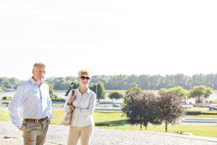 Confident middle-aged couple standing at park against clear sky Royalty Free Stock Photos