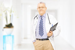 Confident middle aged doctor holding a clipboard in a hospital Stock Images