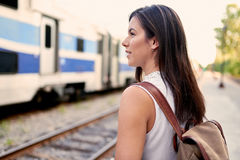 Confident millennial student on the go checking her smart phone on a train platform Royalty Free Stock Image