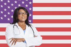Confident mixed race female surgeon looking away over American flag Royalty Free Stock Photo