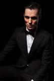 Confident model in black suit posing seated in dark. Portrait of confident handsome model in black suit posing seated while looking at the camera in dark studio stock photography