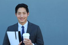 Confident modern business man holding to go cup of coffee or tea and folder with documents stock photos