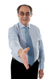 Confident modern businessman offering handshake. Businessman offering handshake to you, studio shot Stock Images