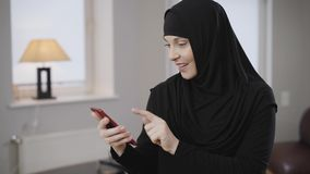 Confident modern muslim woman in traditional black hijab sending message on smartphone. Satisfied eastern lady scrolling