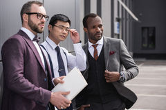 Confident multicultural business team standing near office and looking aside. Portrait of confident multicultural business team standing near office and looking royalty free stock photos