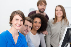 Confident multiethnic young business team. Lead by a smiling attractive young women working together in the office at a desktop computer royalty free stock image