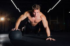 Confident muscled man doing push up from MEDICINE ball in gym. Young bodybuilder fitness trainer model doing exercises in the loft Stock Image
