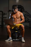 Confident Muscled Man In Gym Using Laptop Royalty Free Stock Images