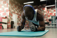 Confident muscled young man wearing sport wear and doing plank position while exercising on the floor in. Confident muscled young black man wearing sport wear Royalty Free Stock Photos