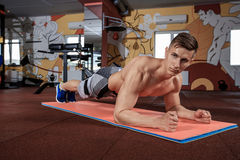 Confident muscled young man wearing sport wear and doing plank position while exercising on the floor at the gym Stock Image