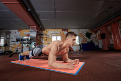 Confident muscled young man wearing sport wear and doing plank position while exercising on the floor at the gym Stock Photography