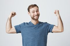 Confident muscular man with stubble, shows muscles on his arms, feels proud to be strong and have strength, says: I am. Hero. Successful smiling male model Stock Photography