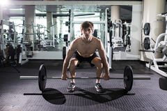 Confident muscular man training squats with barbells over head. Closeup portrait of professional man workout with barbell at gym. stock images