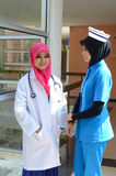Confident Muslim doctor and nurse busy conversation at hospital