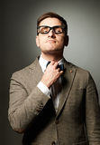 Confident nerd in eyeglasses adjusting his bow-tie Stock Photos