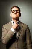 Confident nerd in eyeglasses adjusting his bow-tie Royalty Free Stock Photos