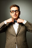 Confident nerd in eyeglasses adjusting his bow-tie Royalty Free Stock Photo