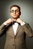 Confident nerd in eyeglasses adjusting his bow-tie Stock Image