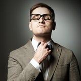Confident nerd in eyeglasses adjusting his bow-tie Stock Photo