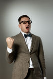 Confident nerd in eyeglasses and bow tie enjoying success Royalty Free Stock Photography