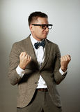 Confident nerd in eyeglasses and bow tie enjoying success Royalty Free Stock Images