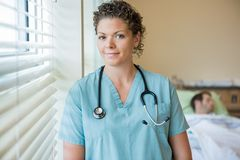 Confident Nurse With Patient In Background Royalty Free Stock Photo