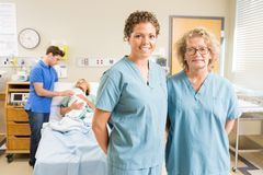 Confident Nurses Standing Against Couple With Baby Stock Image