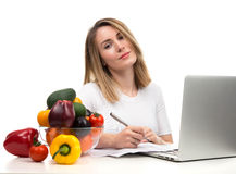 Confident nutritionist woman working at desk with fresh fruits a Royalty Free Stock Images