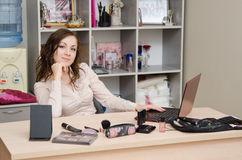 Confident office specialist. A young girl puts makeup in the office workplace Stock Images