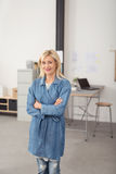 Confident Office Woman Crossing Arms Over Stomach. Confident Blond Office Woman in Blue Long Sleeved Coat and Jeans, Crossing her Arms Over Stomach While Smiling Royalty Free Stock Image