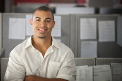 Confident Office Worker. Smiles in his office cubicle Royalty Free Stock Photography