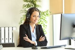 Confident office worker with headset looks at camera stock photo