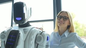Confident office worker touching shoulder of robot and smiling stock video footage
