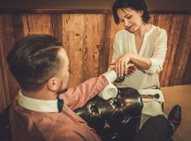 Confident old-fashioned man doing male manicure in a Barber shop. Royalty Free Stock Photography