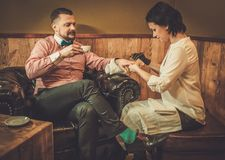 Confident old-fashioned man doing male manicure in a Barber shop. Stock Images