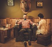 Confident old-fashioned man with glass of whisky doing male manicure in a Barber shop. Royalty Free Stock Photos