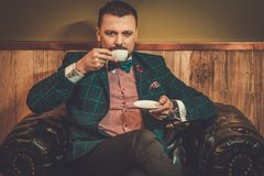 Confident old-fashioned man sitting in comfortable leather chair with cup of coffee in wooden interior at Barber shop. Stock Photo