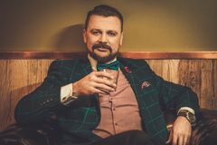 Confident old-fashioned man sitting in comfortable leather chair with glass of whisky in wooden interior at Barber shop. Royalty Free Stock Image