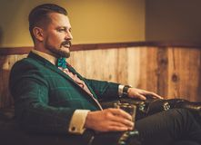 Confident old-fashioned man sitting in comfortable leather chair with glass of whisky in wooden interior at Barber shop. Royalty Free Stock Photography