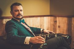 Confident old-fashioned man sitting in comfortable leather chair with glass of whisky in wooden interior at Barber shop. stock photography