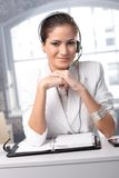 Confident operator with headset. Confident customer service operator at office desk wearing headset, smiling at camera royalty free stock photo