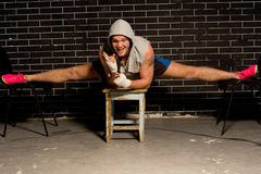 Confident optimistic supple boxer working out. During a training session balancing across three stools with his legs splayed in the splits to strengthen and Royalty Free Stock Image