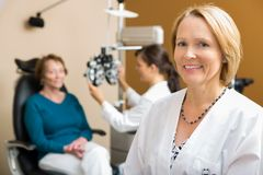 Confident Optometrist With Colleague Examining Stock Images